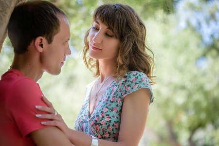 Szczęśliwa para na wakacjach. Kochankowie się śmieją. Szczęśliwy facet i dziewczyna. Miłośnicy cieszą się sobą w wieczornym parku. Zdjęcie Seryjne