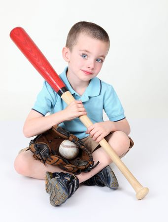 Preschool boy sitting down holding bat in studio photo
