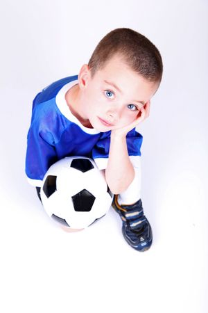 Kneeling boy with soccer ball