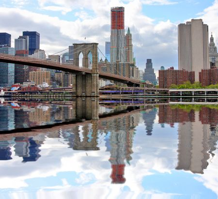Brooklyn bridge and lower Manhattan reflected in East River Stock Photo