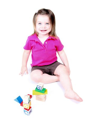 Toddler girl playing with childrens blocks on white background
