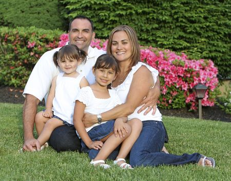 Good looking family outdoor portrait with flowers in background  photo