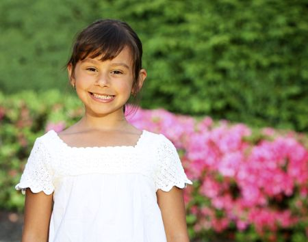 Pretty preschool girl standing in garden portrait
