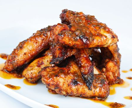 Hot grilled chicken wings on white plate with drizzle of sauce