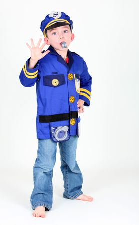 Young boy dressed up as a police officer who is blowing a whistle on white background. Stock Photo