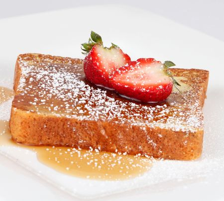 French toast with powdered sugar and a strawberry on white