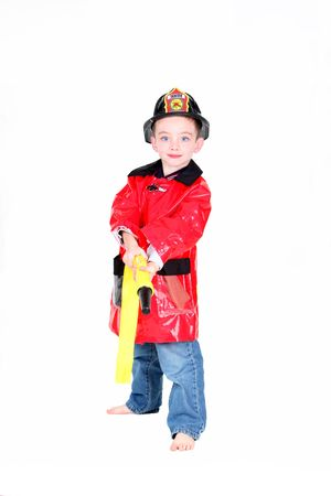 Preschool age boy in fireman costume with hose on white background