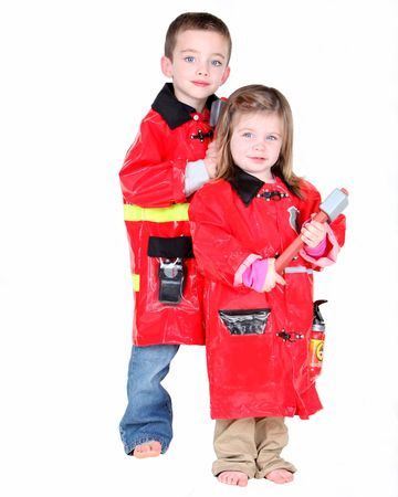 Two young children dressed as firemen on white background photo