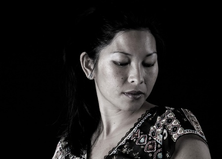 Asian woman looking down on black background photo