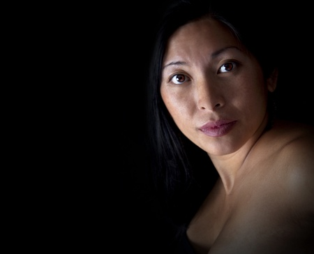 Asian woman looking at camera on black background photo