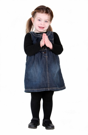 Pretty toddler girl with hands in prayer on white background