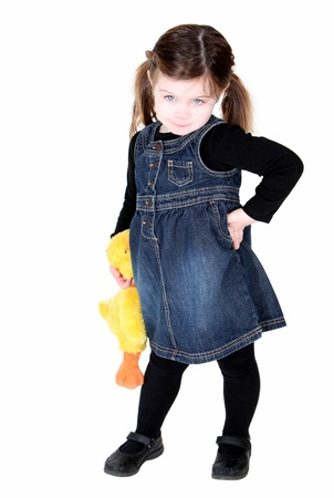 Pretty toddler girl with hand on hips and stuffed animal showing attitude