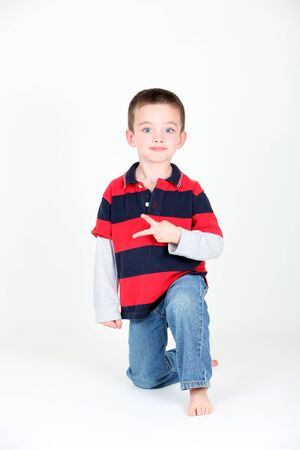 Young preschooler kneeling on white background making a peace sign