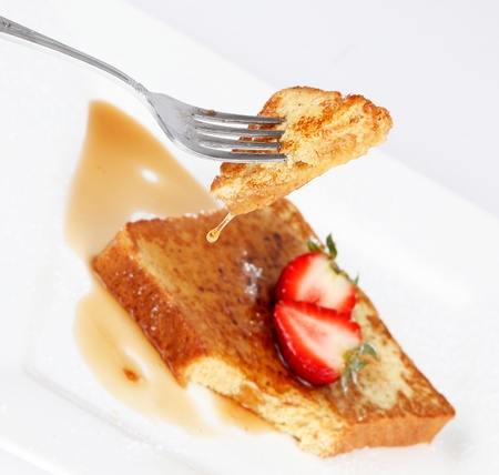 French toast with drip of syrup and strawberries on white background  Stock Photo