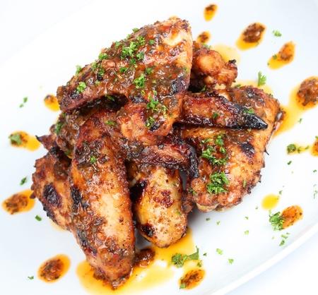 alitas de pollo: Alas de pollo a la brasa caliente en el plato blanco con pinceladas de salsa