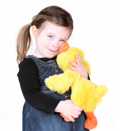 stuffed animals: Little girl hugging her stuffed toy on white Stock Photo