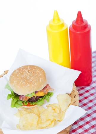 red tablecloth: Bacon Cheeseburger and chips  in a basket with a checkered tablecloth and ketchup and mustard bottles