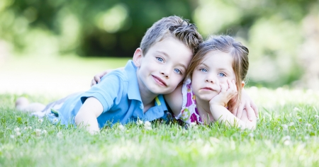 brother sister: Two children laying in the grass while embracing Stock Photo