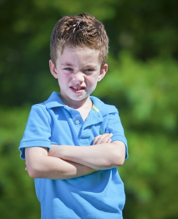brat: Angry boy with crossed arms outdoor portrait