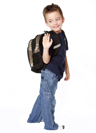 Young boy with backback waving goodbye Stock Photo