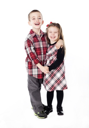 siblings embracing in holiday clothes in studio isolated on white photo