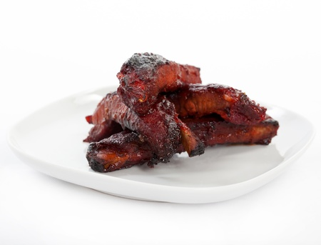 Chinese spare ribs on a plate isolated on white.