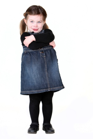 sassy: sassy child with arms folded on white with copyspace. Stock Photo