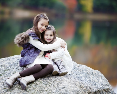 Hispanic sisters embracing on a rock outdoors Stock Photo
