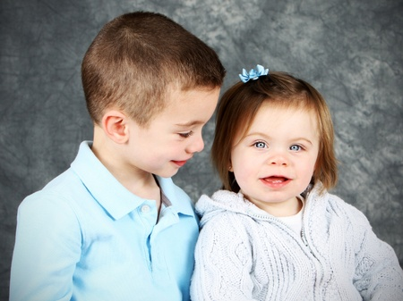 Young boy looking adoringly at little girl in studio photo