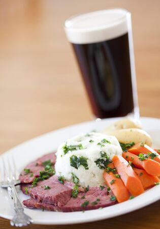st patty day: Traditional Corned Beef Dinner with Beer on a table Stock Photo