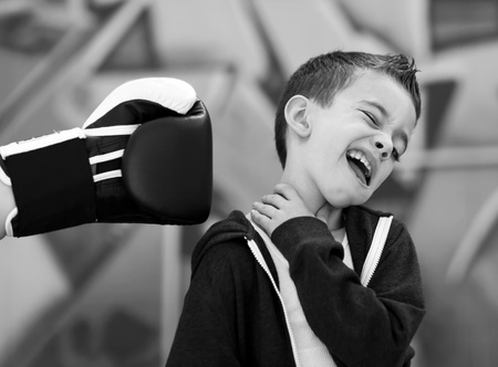 cool guy: Young boy bing punched in face with boxng glove Stock Photo