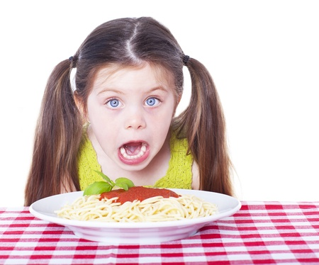 little table: Beautiful girl eating pasta isolated on white Stock Photo