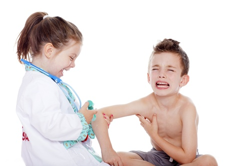 stethoscope: Young girl doctor laughing as she gives a shot to young boy Stock Photo