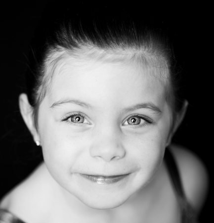 Beautiful close up of a toddler ballerina on black background Stock Photo