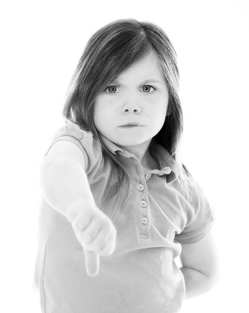 Young girl with thumbs down in studio on white photo