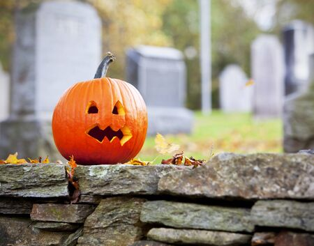 Pumpkin in graveyard with autumn leaves photo
