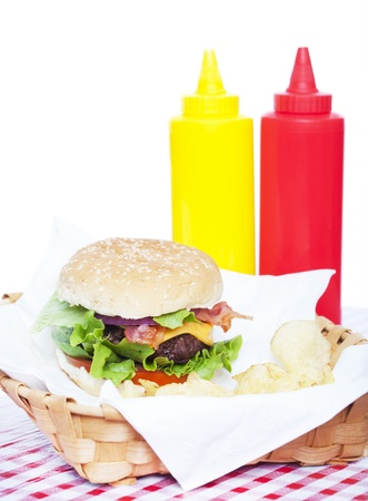 tomato catsup: Bacon Cheeseburger and chips in a basket with a checkered tablecloth and ketchup and mustard bottles