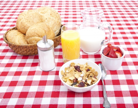 Breakfast of cereal, fruit, rolls, orange juice and milk on tablecloth photo