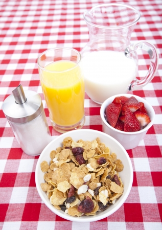 cornflakes: Breakfast of cereal, fruit, orange juice and milk on tablecloth