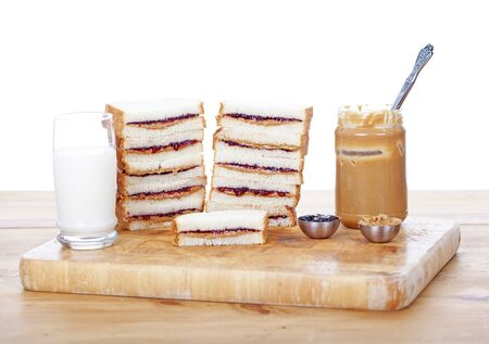 peanut butter and jelly sandwich: Stacks of peanut butter and jelly sandwiches on white
