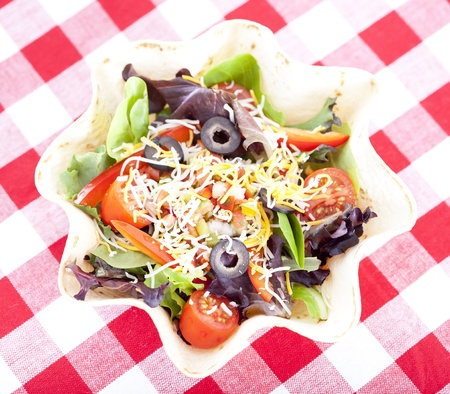 melted cheese: Taco salad on checkered tablecloth