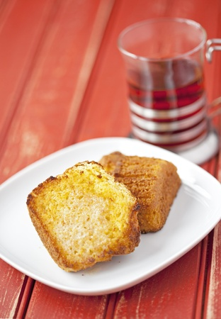cornbread: Toasted corn muffin with butter and a cup of teaon a wooden table Stock Photo