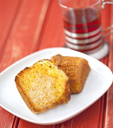 cornbread: Toasted corn muffin with butter and a cup of tea on a wooden table