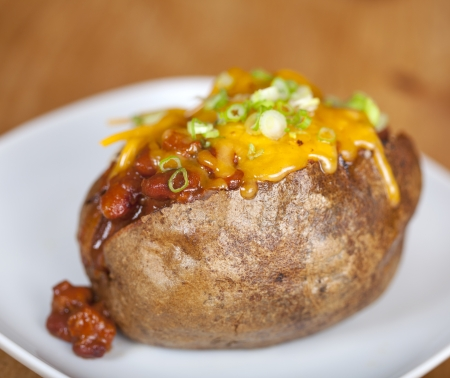 Loaded baked potato with chili and cheese on a plate