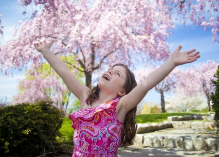 Young girl taking a deep breath enjoying freedom with arms in the air photo