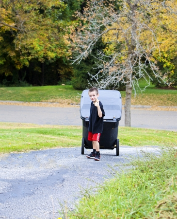 Handsome young boy bringing trash can up the driveway