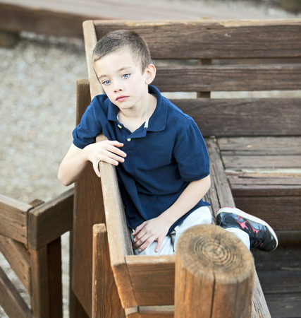 Very sad handsome boy sitting in the park Stock Photo
