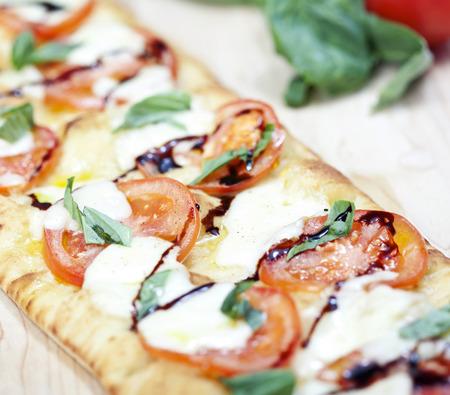 Fresh pizza with tomato, mozzarella and basil on wooden board