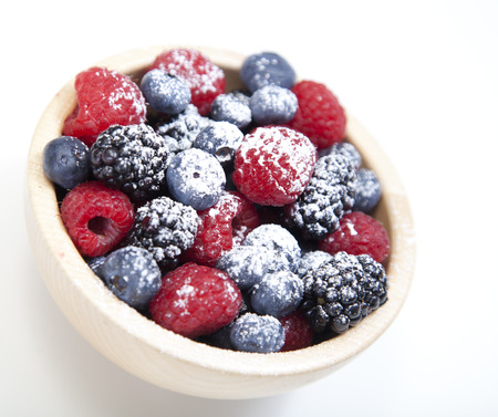 Assorted mixed berries in a bowl isolated on white