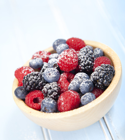 Assorted mixed berries in a bowl on wooden background Stock Photo